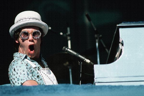 Elton John plays the piano during a performance.