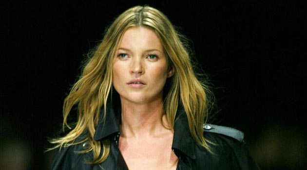 """(FILES) British supermodel Kate Moss displays an outfit by Burberry Prorsum collection during the Milan 2004 Spring/Summer fashion week, 30 September 2003. Moss will not be charged over allegations that she took cocaine because of """"insufficient evidence"""", the British Crown Prosecution Service (CPS) said Thursday, 15 June 2006. But the CPS, which had been considering whether to press charges against the 32-year-old catwalk star, said there was """"an absolutely clear indication"""" she was using and providing drugs. The announcement comes following an investigation into the claims following the Daily Mirror ´s publication last September of grainy still photographs from video footage of Moss allegedly taking drugs at a west London recording studio. AFP PHOTO/PAOLO COCCO"""