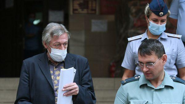 Михаил Ефремов после судебного заседания с документами в руках