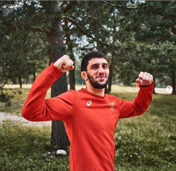 Улыбающийся Заур Сидаков демонстрирует свою силу в красной толстовке
