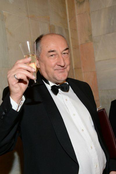 Борис Клюев в классическом костюме с бабочкой поднимает бокал с шампанским
