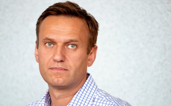 Алексей Навальный с задумчивым взглядом в клетчатой рубашке