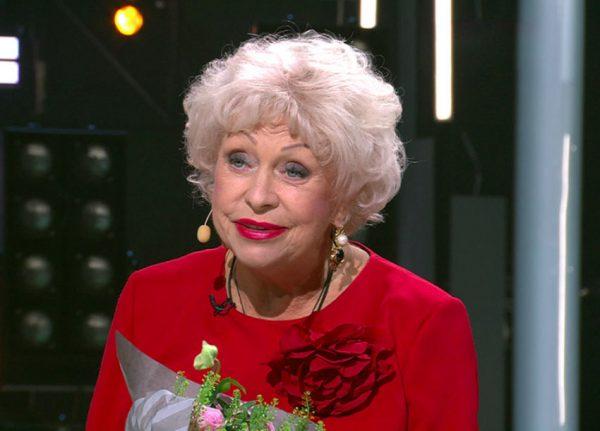 Людмила Поргина с букетом цветов в красном платье