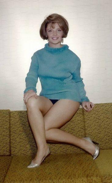 На фото Наталья Кустинская в голубой кофте и в туфлях на каблуках
