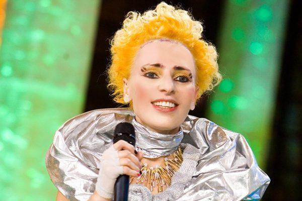 Жанна Агузарова на сцене с микрофоном, с желтыми волосами и ярким макияжем