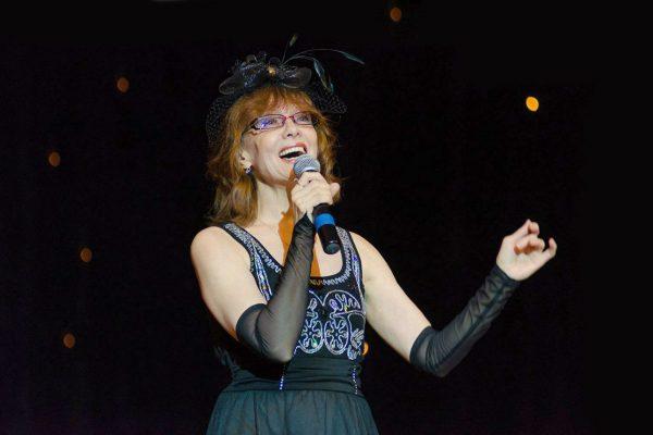 Ольга Зарубина на сцене с микрофоном в черном платье и кружевной шляпе