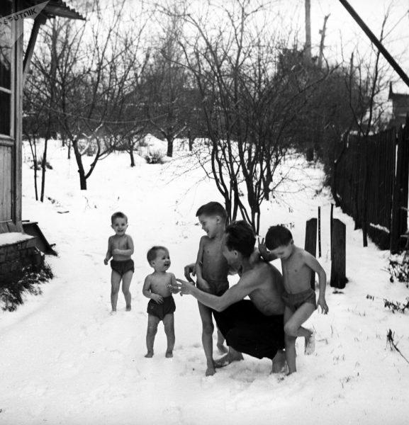 Борис Никитин с босоногими детьми на снегу