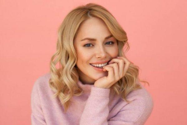 Зоя Бербер в розовом свитере улыбается