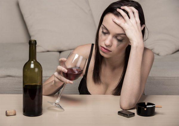Девушка плачет с бокалом и бутылкой вина